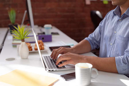 Midsection of caucasian businessman sitting at desk in office using laptop. working in business at a modern office.
