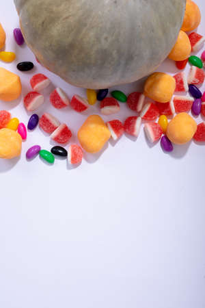 Composition of halloween pumpkin and trick or treat sweets with copy space on white background. halloween tradition and celebration concept.