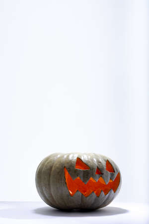 Composition of lit scary halloween carved green pumpkin with copy space on white background. halloween tradition and celebration concept.