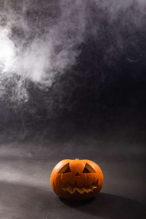 Composition of halloween carved pumpkin and cloud of smoke with copy space on black background. halloween tradition and celebration concept.