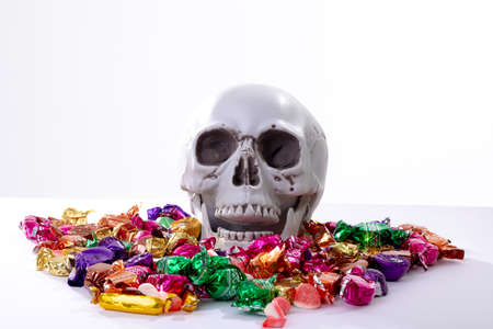 Composition of halloween laughing skull with trick or treat sweets on white background. halloween tradition and celebration concept. Stock fotó