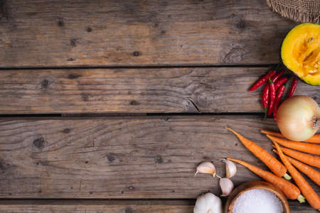 Composition of autumn halloween carrots, peppers, pumkin, garlic with copy space on wood. autumn, halloween tradition, food, cooking and celebration concept. Stock fotó
