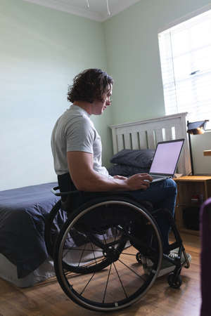 Rear view of disabled man sitting on wheelchair using laptop with copy space on couch at home. disability and handicap concept