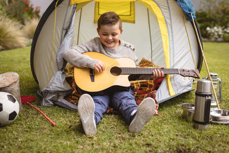 Caucasian boy smiling while playing guitar sitting in a tent in the garden. childhood and hobby concept