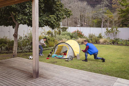 Caucasian father and son smiling while setting up a tent together in the garden. fatherhood and love concept