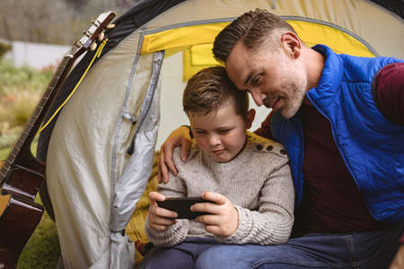 Caucasian father and son using smartphone while sitting in a tent in the garden. fatherhood and love concept Stock fotó