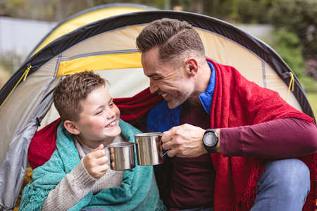 Caucasian father and son smiling while toasting their coffee cups sitting in a tent in the garden. fatherhood and love concept