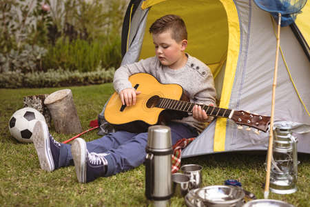 Caucasian boy playing guitar while sitting in a tent in the garden. childhood and hobby concept Stock fotó