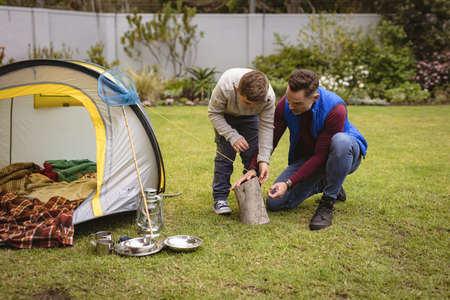 Caucasian father and son setting up a tent together in the garden. fatherhood and love concept
