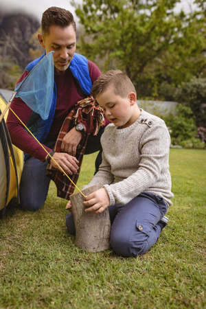 Caucasian father watching while his son setting up a tent in the garden. fatherhood and love concept