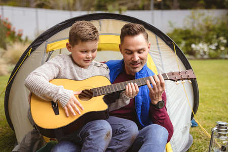 Caucasian father and son playing guitar together while sitting in a tent in the garden. fatherhood and love concept