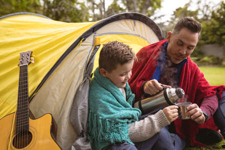 Caucasian father and pouring coffee in a cup for his son while sitting in a tent in the garden. fatherhood and love concept Stock fotó