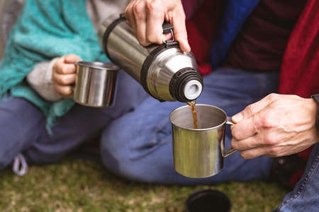 Mid section of man pouring coffee in a cup while sitting in a tent in the garden. fatherhood and love concept