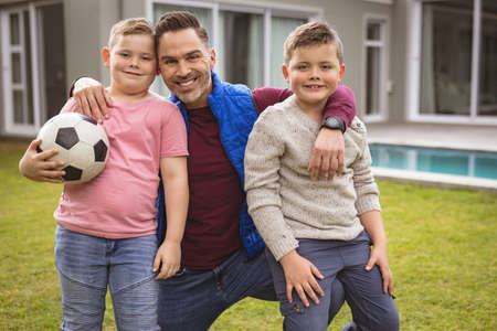 Portrait of caucasian father and two sons smiling while holding football in the garden. fatherhood and love concept