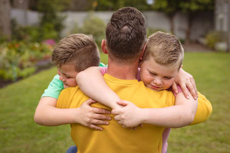 Close up view of caucasian father hugging his two sons in the garden. fatherhood and love concept