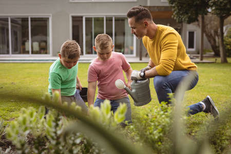 Caucasian father and two sons watering plants together in the garden. fatherhood and gardening hobby concept Stock fotó