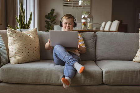 Caucasian boy wearing headphones using laptop sitting on the couch at home. home schooling and education concept