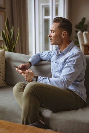 Thoughtful caucasian man using smartphone sitting on the couch at home. working from home during coronavirus covid-19 pandemic concept Stock fotó