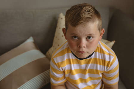 Portrait of caucasian boy looking up while sitting on the couch at home. childhood and home concept Stock fotó