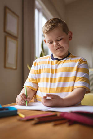 Caucasian boy drawing in his book sitting in the living room at home. childhood and hobby concept Stock fotó
