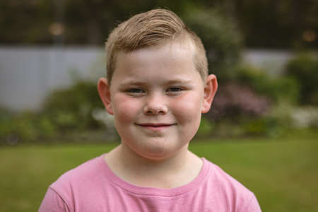 Portrait of caucasian boy smiling while standing in the garden. childhood, hobby and sport concept Stock fotó