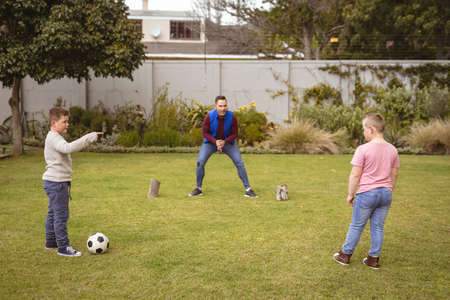 Caucasian father and two sons playing football together in the garden. fatherhood and love concept Stock fotó