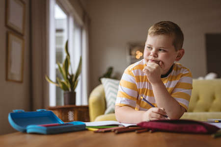 Thoughtful caucasian boy drawing in his book sitting in the living room at home. childhood and hobby concept