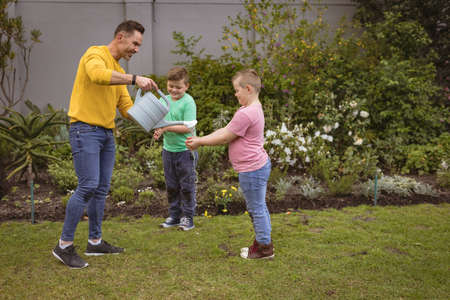 Caucasian father pouring water while two sons washing their hands in the garden. fatherhood and gardening hobby concept