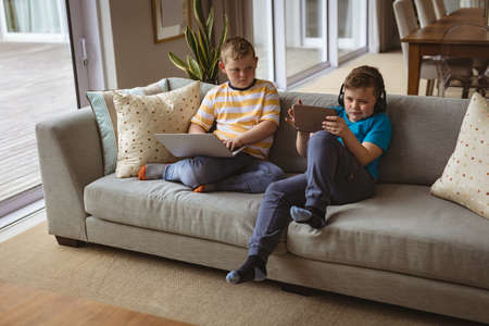 Two caucasian boys using laptop and digital tablet sitting on the couch at home. childhood, technology and home concept