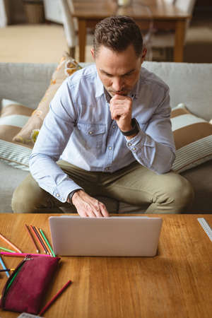 Caucasian man using laptop sitting on the couch at home. working from home during coronavirus covid-19 pandemic concept