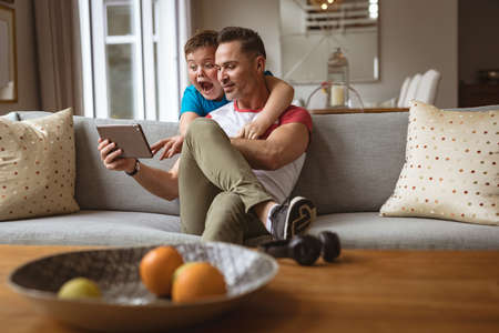 Caucasian father and son using digital tablet on the couch at home. fatherhood, technology and home concept Stock fotó