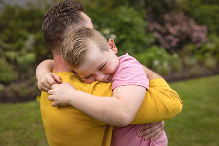 Close up view of caucasian father and son hugging each other in the garden. fatherhood and love concept