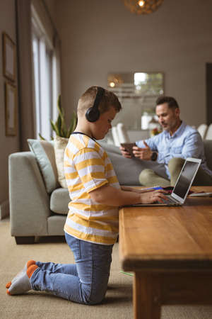 Caucasian boy wearing headphones using laptop in the living room at home. home schooling and education concept Stock fotó