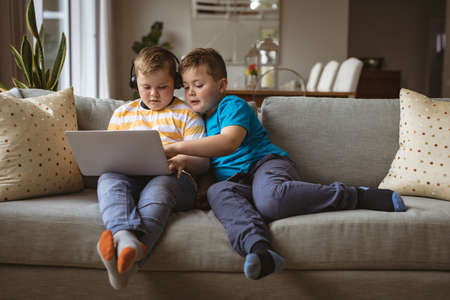 Two caucasian boys using laptop sitting on the couch at home. childhood, technology and home concept
