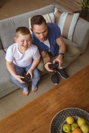 Overhead view of caucasian father and son playing video games sitting on the couch at home. gaming and entertainment concept