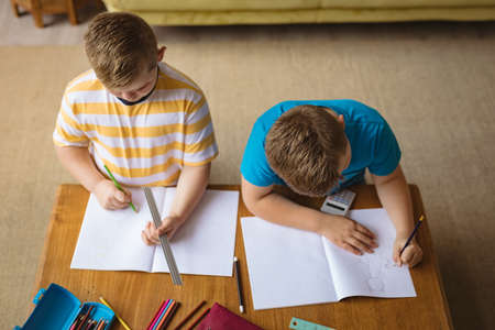 Overhead view of two caucasian boys drawing in their books sitting in the living room at home. childhood and hobby concept Stock fotó