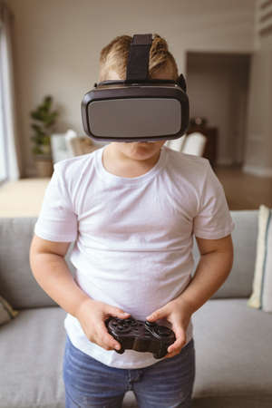Caucasian boy wearing vr headset and holding gaming controller playing video games at home. gaming and entertainment concept Stock fotó