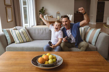 Caucasian father and son celebrating while playing video games sitting on the couch at home. gaming and entertainment concept
