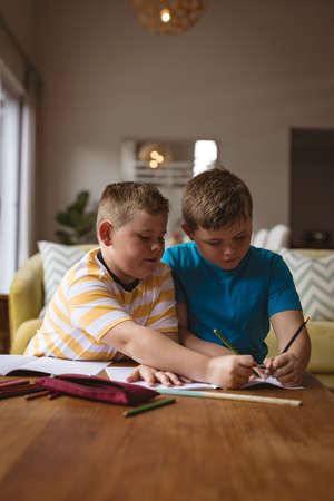 Two caucasian boys drawing together in a book sitting in the living room at home. childhood and hobby concept