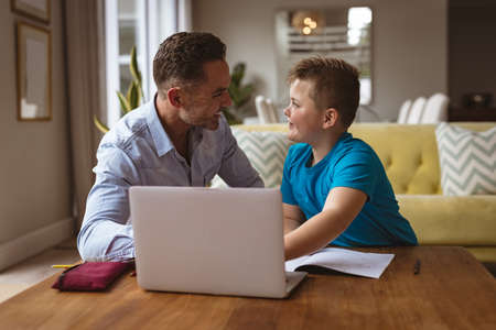 Caucasian father using laptop to help his son with homework at home. home schooling and education concept