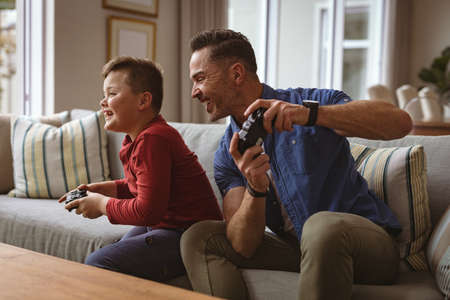 Caucasian father and son playing video games together sitting on the couch at home. fatherhood and love concept