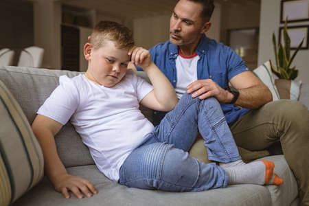 Caucasian father scolding his son sitting on the couch at home. fatherhood and childhood concept Stock fotó