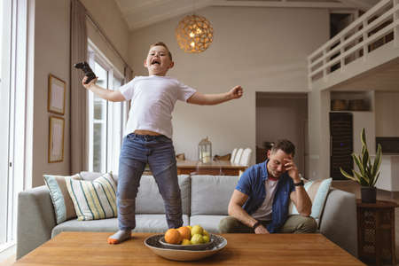 Caucasian boy celebrating standing on the table while playing video games with his father at home. gaming and entertainment concept