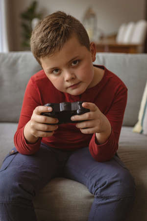 Caucasian boy playing video games sitting on the couch at home. gaming and entertainment concept Stock fotó