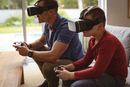 Caucasian father and son wearing vr headsets playing video games sitting on the couch at home. gaming and entertainment concept
