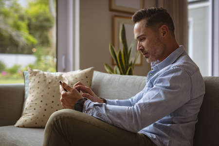 Caucasian man using smartphone sitting on the couch at home. working from home during coronavirus covid-19 pandemic concept Stock fotó