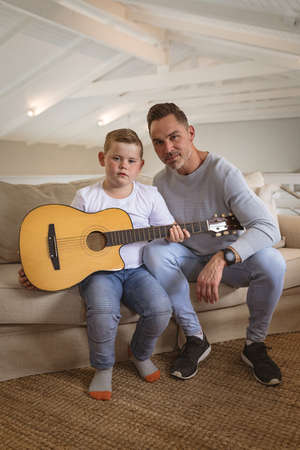 Portrait of caucasian father and son with a guitar sitting on the couch at home. childhood and hobby concept Stock fotó