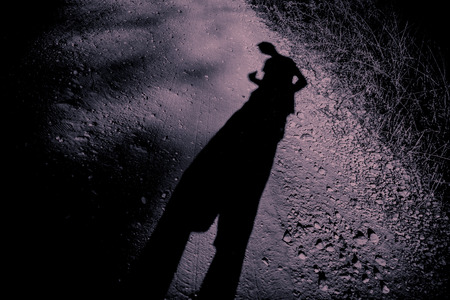 elongated: Elongated shadow of a man on gravel. A surreal ambiance in black and purple.