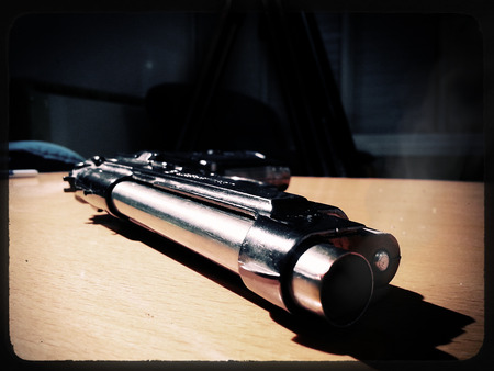 hitman: Silver 9mm pistol lying on a wooden table. Smoke coming from the barrel of the gun. Stock Photo