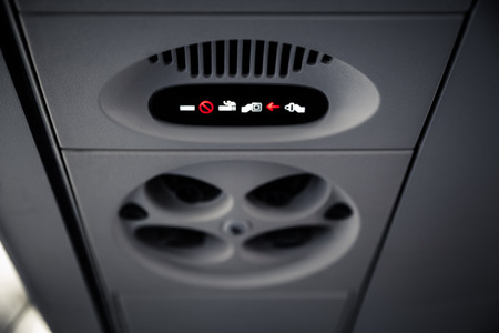 No Smoking and Fasten Seatbelt sign Inside an airplane. Overhead console in the modern passenger aircraft. photo